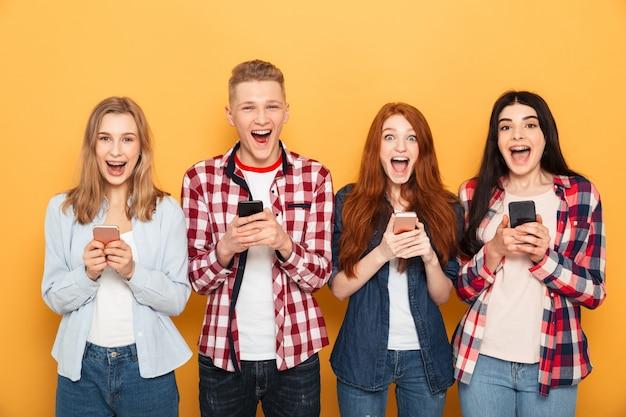 Gruppo di amici di scuola eccitati che tengono i telefoni cellulari Foto Premium