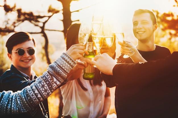 Gruppo di giovani entusiasti sorridenti e tintinnio di bicchieri di alcol mentre festeggiava in una splendida campagna Foto Premium