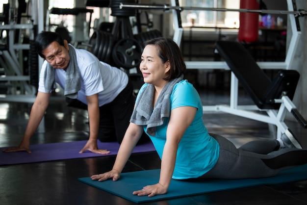 Gruppo di esercizio d'allungamento senior asiatico dell'amico alla palestra di yoga. stile di vita sano degli anziani. Foto Premium