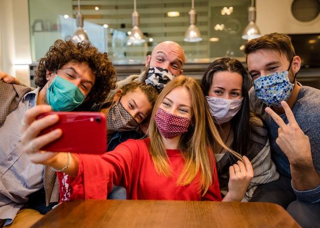 Gruppo di amici coperti da maschera facciale al ristorante Foto Premium