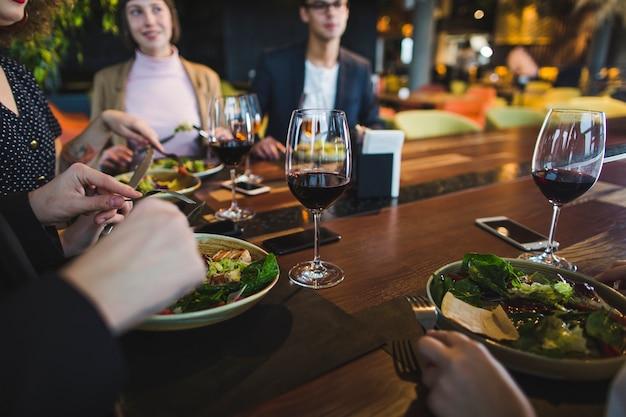 Gruppo di amici che mangiano nel ristorante Foto Premium
