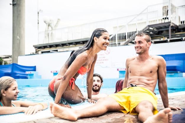 Gruppo di amici che fanno festa in piscina Foto Premium