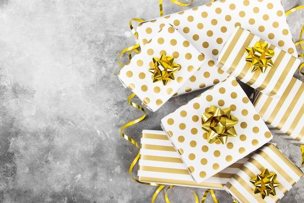 Gruppo di regali in carta bianca e oro su grigio, vista dall'alto, copia spazio Foto Premium