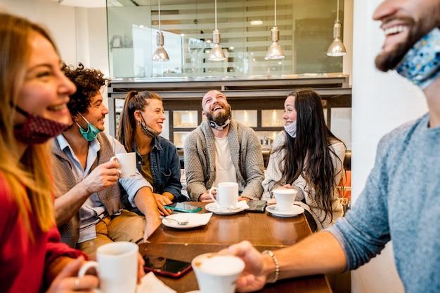 Gruppo di amici felici con la maschera per il viso che beve caffè espresso al caffè Foto Premium
