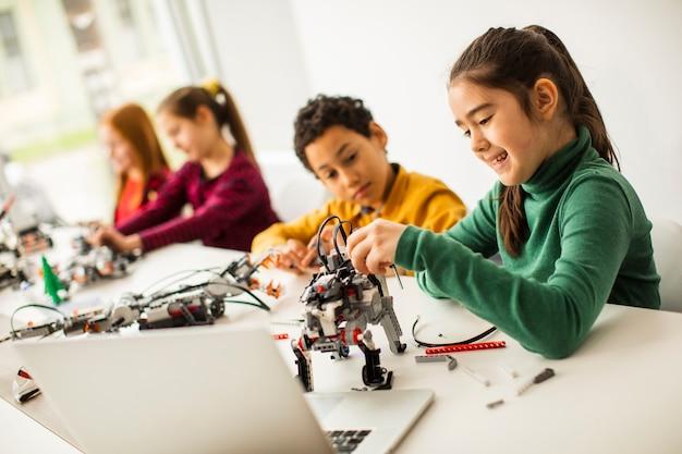 Gruppo di bambini felici che programmano giocattoli elettrici e robot in aula di robotica Foto Premium
