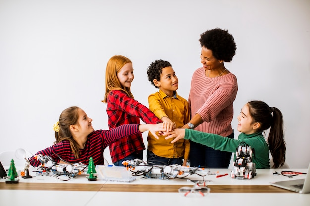 Gruppo di bambini felici con il loro insegnante di scienze femminile afroamericano che programma giocattoli elettrici e robot all'aula di robotica Foto Premium