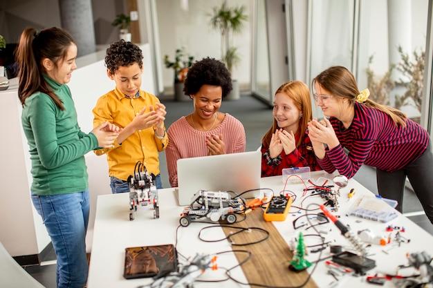 Gruppo di bambini felici con il loro insegnante di scienze femminile afroamericano con laptop che programmano giocattoli elettrici e robot in aula di robotica Foto Premium