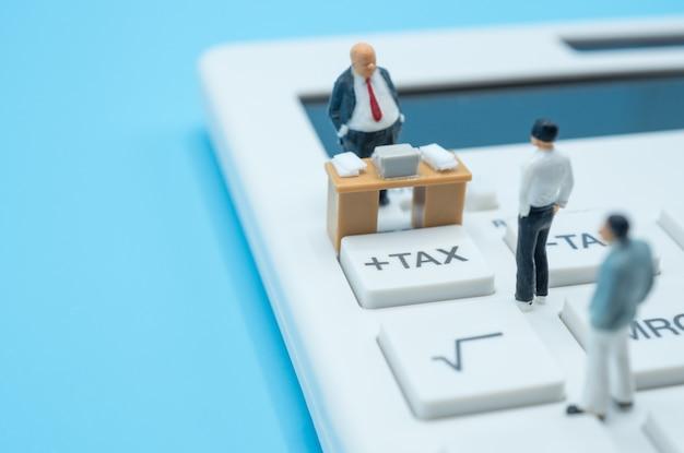Un gruppo di uomini d'affari in miniatura si trova sul pulsante fiscale della calcolatrice, considera l'impatto dell'epidemia di covid-19 su economia, finanza, reddito e tasse. Foto Premium