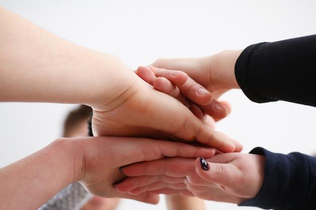 Gruppo di persone in giacca e cravatta incrociate le mani in pila per la vittoria Foto Premium