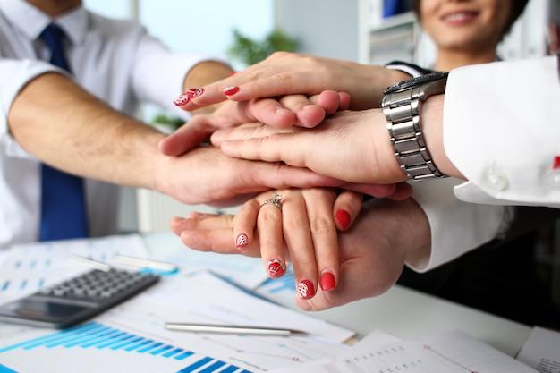 Gruppo di persone in giacca e cravatta incrociate le mani nel mucchio Foto Premium