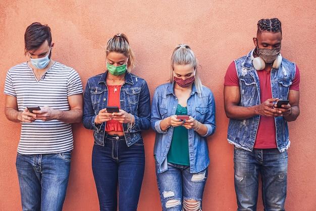 Gruppo di persone che utilizzano i propri smartphone in covid-19 volte protette con maschera facciale Foto Premium