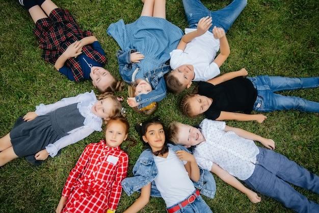 Un gruppo di scolari giace sull'erba in cerchio e si diverte Foto Premium