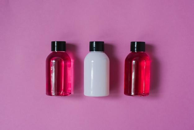 Gruppo di piccole bottiglie da viaggio per la cura del corpo: bagnoschiuma, shampoo, balsamo, lozione su sfondo rosa. la composizione dello strato piatto di cosmetici Foto Premium