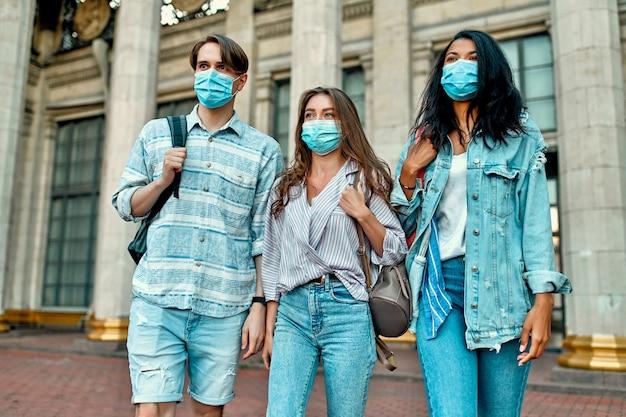 Un gruppo di studenti che indossano maschere mediche protettive vicino al campus. Foto Premium