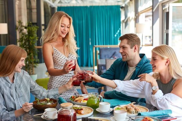 Un gruppo di giovani caucasici festeggia il compleanno con un bicchiere di bevanda tintinnante Foto Premium