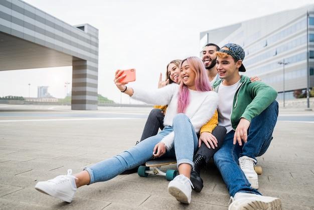 Gruppo di giovani amici che prendono un selfie in città Foto Premium