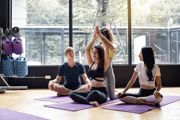 Gruppo di giovani che fanno yoga su una stuoia di yoga con un istruttore che insegna gradualmente. Foto Premium