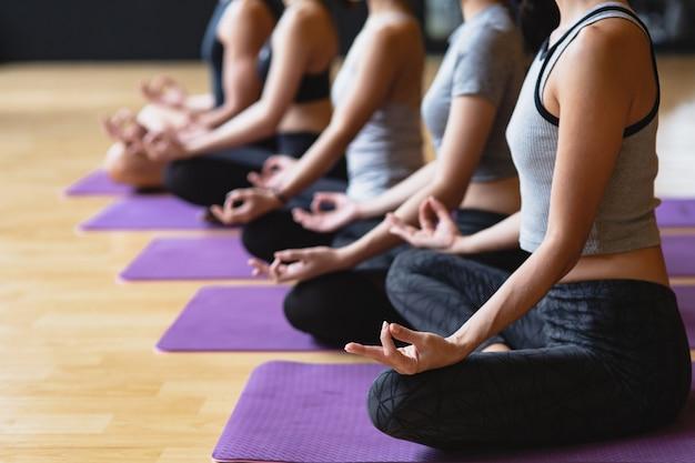 Il gruppo di giovani sportivi che praticano la classe di yoga che fa la posa del loto di meditazione con lo spazio della copia, lo yoga e la forma fisica risolvono lo stile di vita di sanità nel club di forma fisica Foto Premium