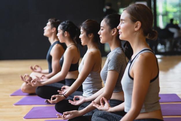 Il gruppo di giovani sportivi che praticano la classe di yoga che fa il loto di meditazione posa con lo spazio della copia Foto Premium