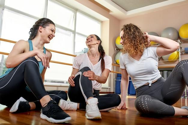 Gruppo di giovani sorridenti sportivi che si siedono sul pavimento Foto Premium