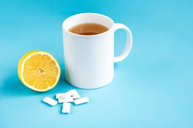 Gomma al limone e tazza di tè su sfondo blu. pulizia e protezione dei denti. Foto Premium
