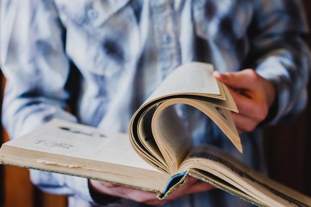 Un ragazzo con una camicia blu sfoglia le pagine di un vecchio libro contro la biblioteca. lo studente cerca di acquisire nuove conoscenze. concetto per la giornata mondiale del libro Foto Premium