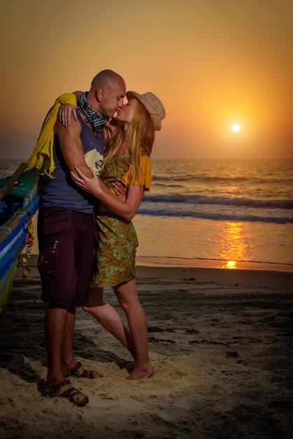 Ragazzo e ragazza vicino alla vecchia barca di legno sulla costa dell'oceano. Foto Premium