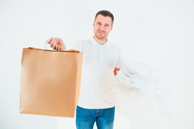 Guy tiene i sacchetti di plastica in una mano e uno di carta nell'altro. processo di riciclaggio e attenzione all'ambiente. utilizzo rispettabile. Foto Premium