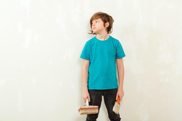 Guy pronto a dipingere il muro nella sua stanza. pennelli felici della tenuta del ragazzo. il figlio aiuta i genitori a dipingere il muro. nuova casa per famiglia. Foto Premium