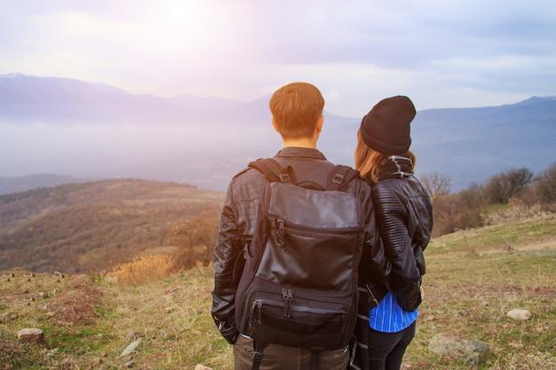 Un ragazzo con uno zaino e una ragazza che guardano le montagne in lontananza Foto Premium