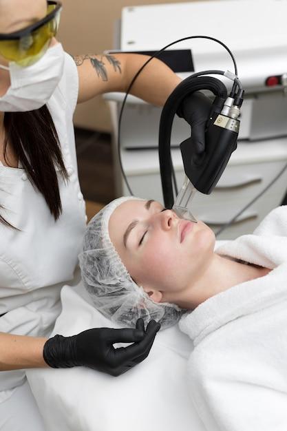 Procedura di cosmetologia di rimozione dei capelli da un terapista presso la clinica spa di bellezza cosmetica. epilazione laser e cosmetologia Foto Premium