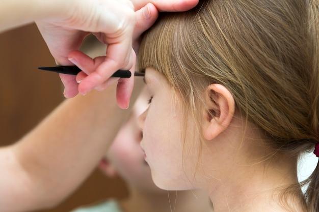 Il parrucchiere sta tagliando i capelli di una bambina nel negozio di barbiere Foto Premium