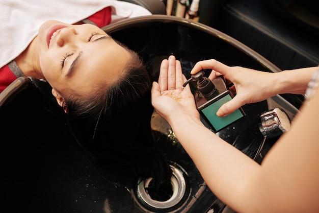 Parrucchiere spremitura shampoo in mano Foto Premium