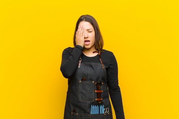 Donna parrucchiere che sembra assonnata, annoiata e che sbadiglia, con un mal di testa e una mano che copre metà del viso Foto Premium