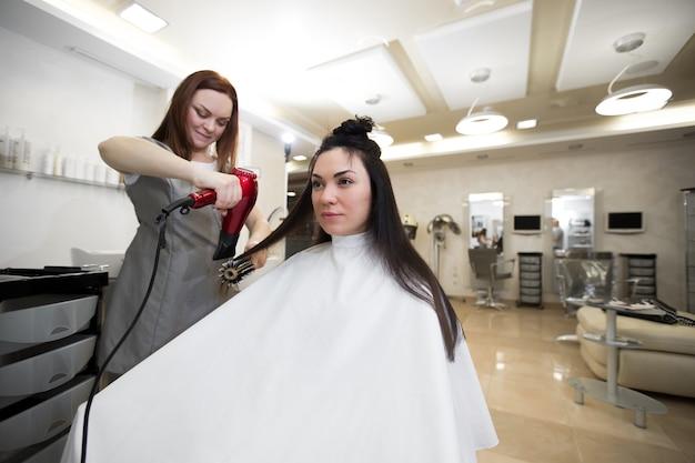 Il parrucchiere lavora con un cliente in un salone di bellezza. il parrucchiere asciuga la ragazza dei capelli bagnati con un asciugacapelli Foto Premium