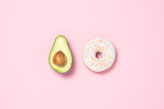 Mezzo avocado e ciambella su uno sfondo rosa. concetto di scelte alimentari. cibo utile o dannoso. minimalismo. vista piana, vista dall'alto. Foto Premium
