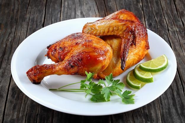 La metà di pollo alla griglia su un piatto Foto Premium