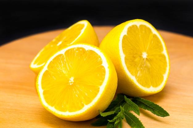 Metà del limone su una tavola di legno. limoni su uno sfondo di legno. limoni. frutta. metà limone menta. concetto di cibo sano. copyspace Foto Premium
