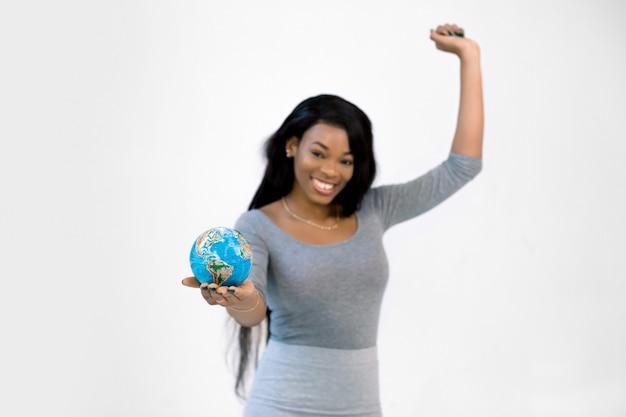 Ritratto di mezza lunghezza di eccitata ragazza africana in abito grigio tenendo una mano in alto, tenendo il globo terrestre del mondo Foto Premium