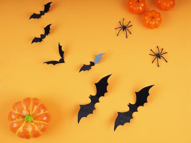Zucche di halloween e pipistrelli con sfondo arancione - composizione piatta di halloween. Foto Premium