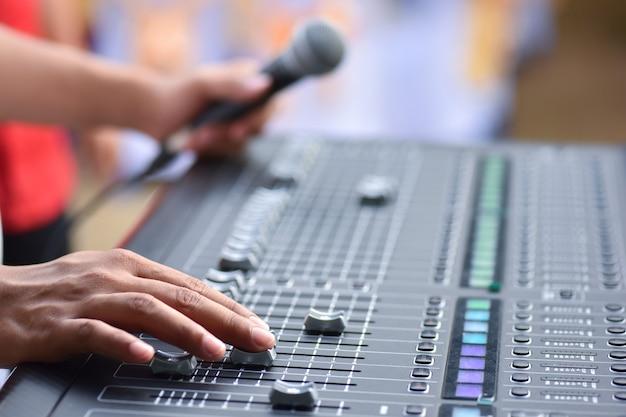 Mano regola il controllo del suono per il controllo del mixer del concerto, ingegnere musicale nel backstage Foto Premium