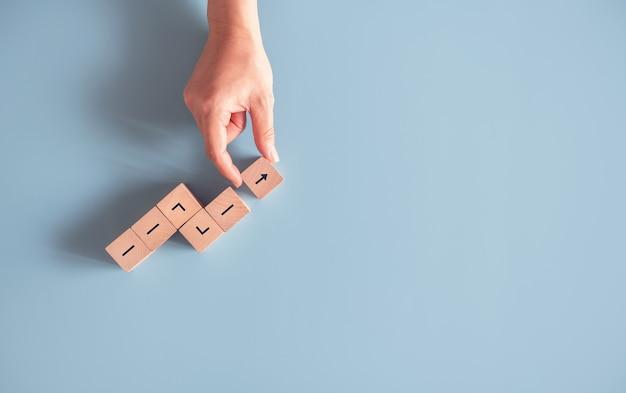 Mano che organizza l'impilamento del blocco di legno come successo di crescita. Foto Premium