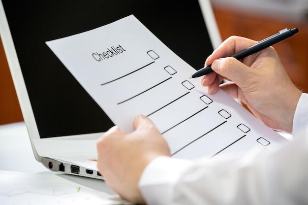 Mano di un uomo d'affari che tiene una penna e controllando la lista di controllo. Foto Premium