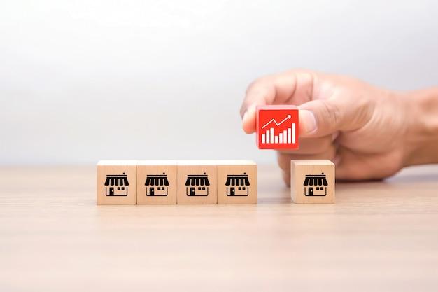 La mano sceglie un blog giocattolo di legno a forma di cubo con il simbolo del grafico commerciale e le icone di marketing in franchising. Foto Premium