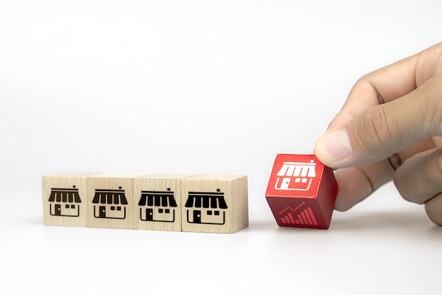 La mano sceglie i blog di legno del giocattolo del cubo con l'icona del negozio di vendita di franchising e l'icona del grafico. Foto Premium