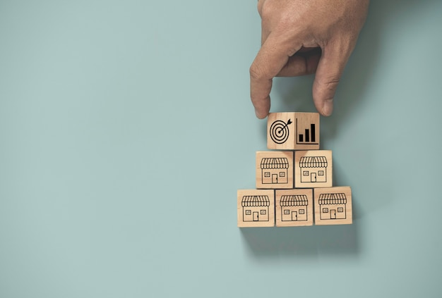 Scorrimento della mano tra il target e la crescita delle vendite nel negozio per lo shopping che stampa lo schermo sul cubo di legno su sfondo blu, espande il concetto di franchising e centro commerciale. Foto Premium