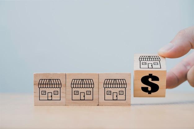 Mano che lancia il blocco cubo di legno per cambiare il negozio in franchising al simbolo del dollaro, espandere il concetto di sviluppo in franchising Foto Premium
