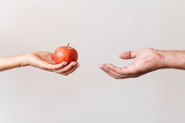 Mano che dà una mela alla persona bisognosa Foto Premium