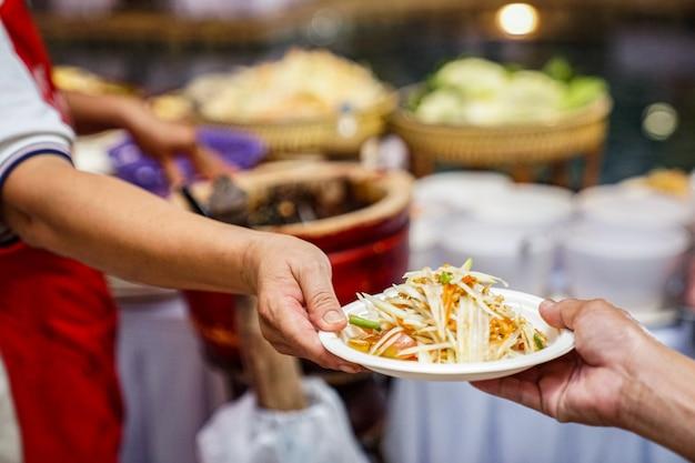 Mano nella mano somtum (piccante insalata di papaya thailandese) famosa insalata locale tradizionale unica al mondo. Foto Premium