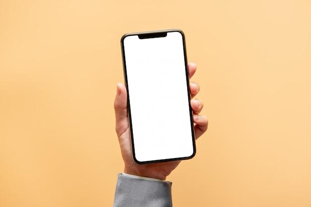 Passi la tenuta dello smartphone nero con lo schermo bianco su fondo giallo. Foto Premium
